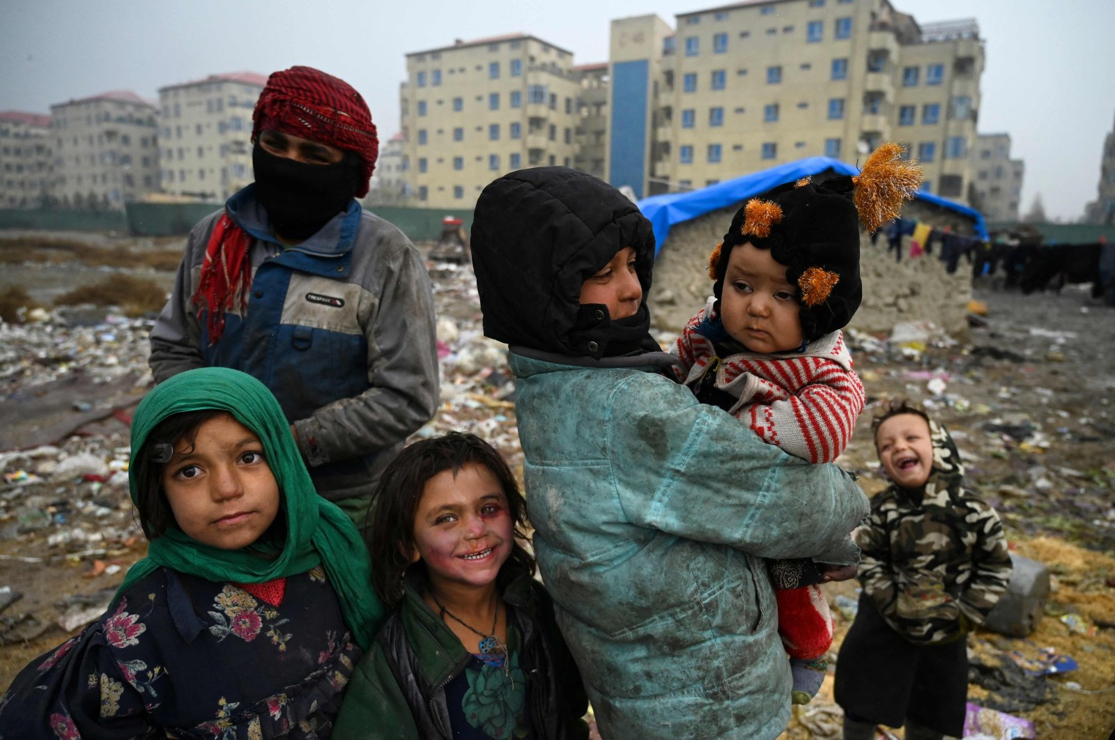Internally displaced Afghan children stand outside their temporary mud house at a refugee camp in Kabul, Afghanistan, November 23, 2020. (AFP Photo)