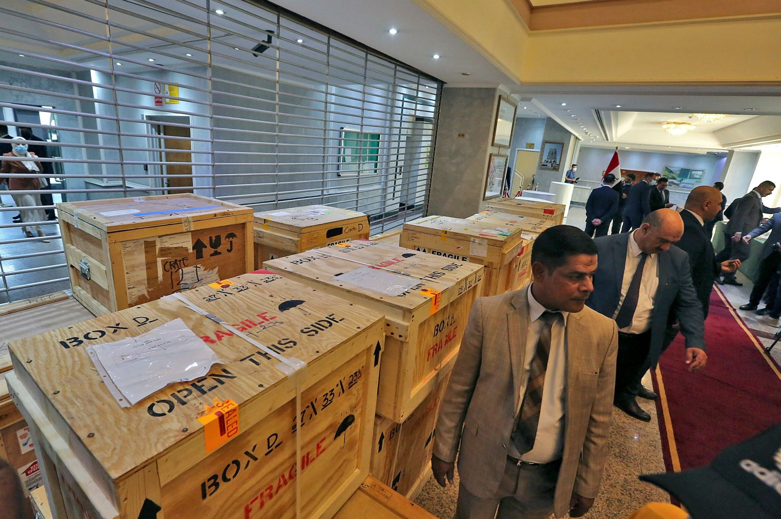 Staff members at Iraq's Ministry of Foreign Affairs work around crates of looted Iraqi antiquities returned by the United States, ahead of a handover ceremony at the ministry in the capital Baghdad, on Aug. 3, 2021. (AFP Photo)