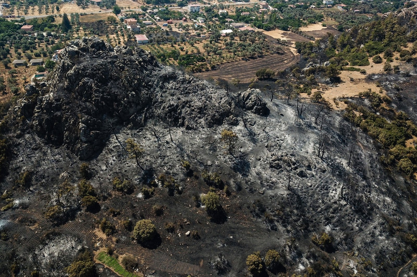 An aerial view shows aravaged area and burnt trees in the Marmaris district ofMuğla, Turkey, Aug. 3, 2021. (AFP Photo)