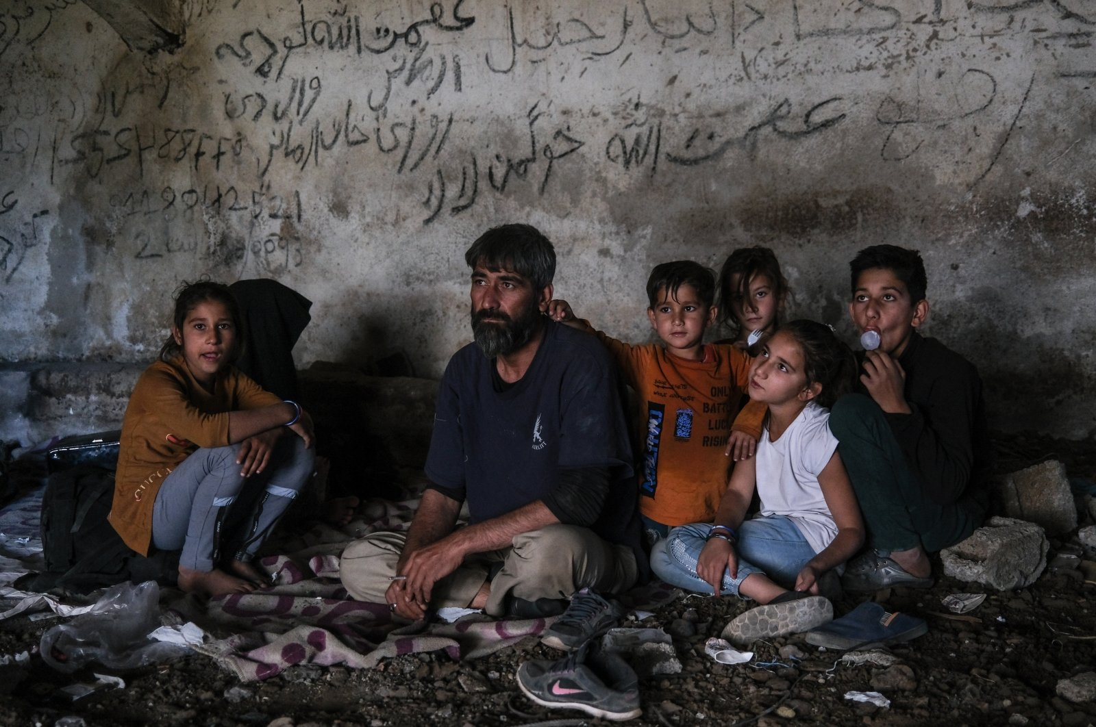 An Afghan family rests in an abandoned shepherd's house near the Turkish city of Van after crossing the Iran-Turkey border, 08 June 2021. (EPA Photo)