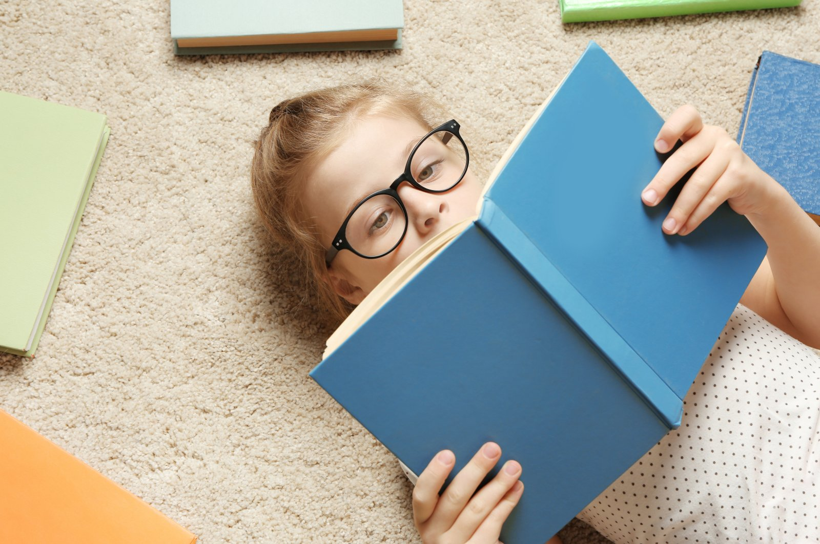 A little girl reading a book while lying on the carpet. (Shutterstock Photo)