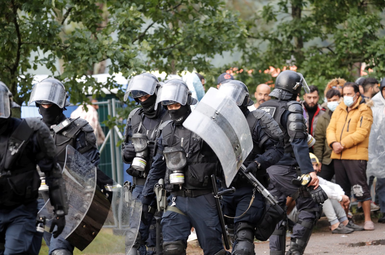 Riot police officers and migrants are seen at the tent camp in the Rudninkai training ground, Lithuania, Aug. 2, 2021. (EPA Photo)