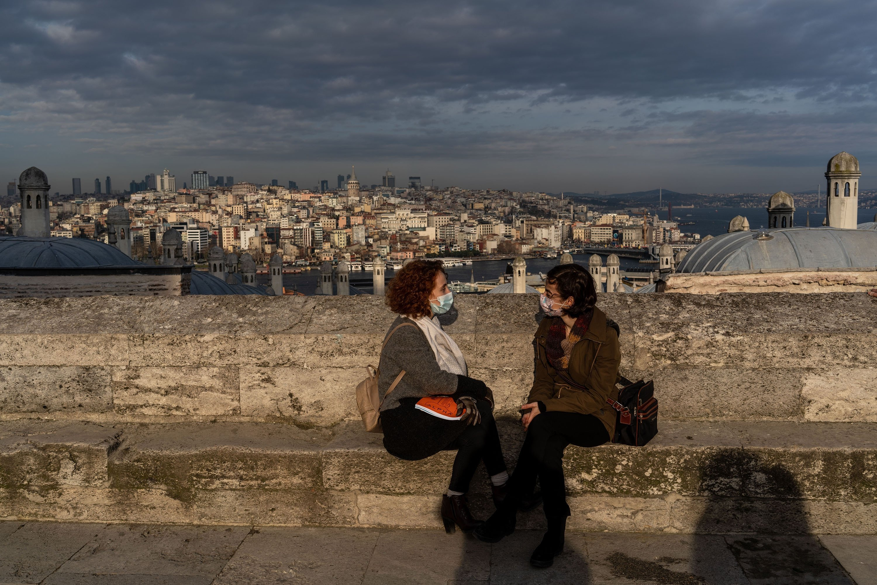 People enjoy the view of the historical peninsula from the garden of the famous Suleymaniye Mosque, in the Süleymaniye district, Istanbul, Turkey on Jan. 22, 2021. (Erhan Demirtas via Getty Images)