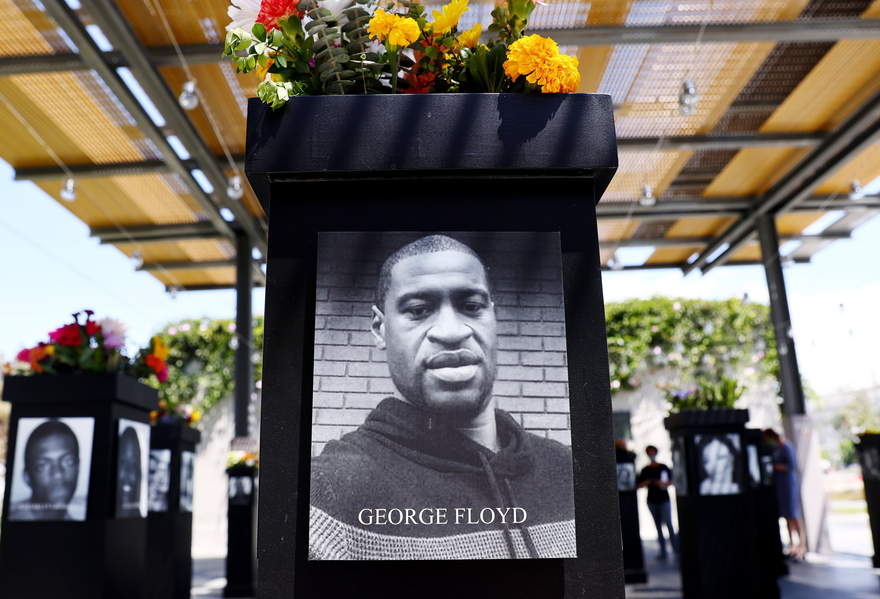 A photograph of George Floyd (C) is displayed along with other photographs at the Say Their Names memorial exhibit at Martin Luther King Jr. Promenade, in San Diego, CA, U.S., July 20, 2021. (Photo by Getty Images)