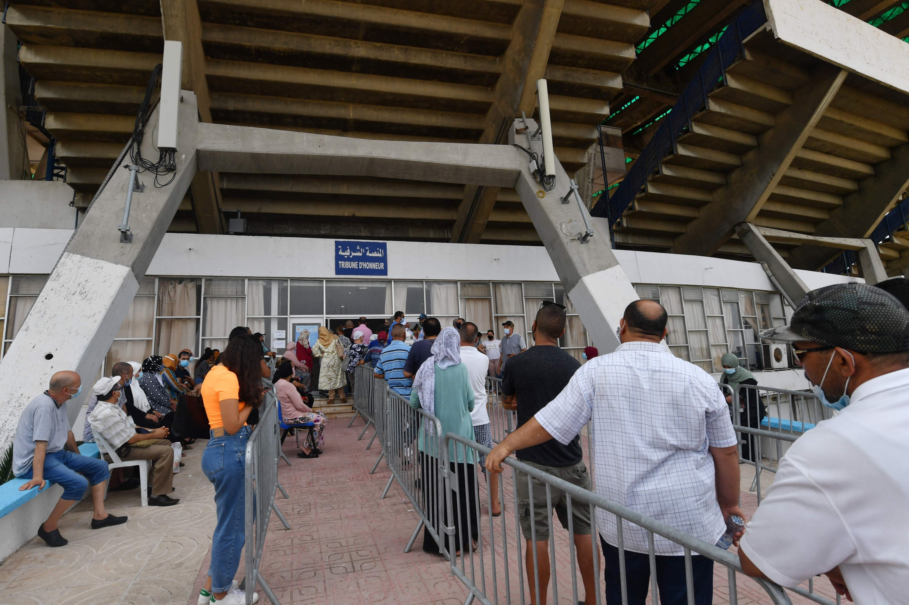People queue to receives their coronavirus vaccines at El-Menzah Stadium which was turned into a vaccination centre in the Tunisian capital Tunis on August 3, 2021. (AFP Photo)