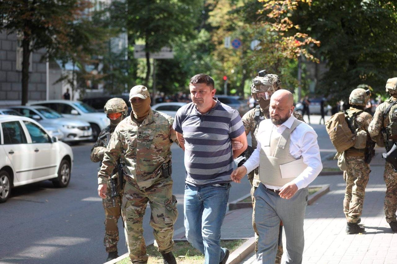 Law enforcement officers detain a man who, according to the head of the National Police, forced his way into Ukraine's main government building and threatened to detonate a grenade, Kyiv, Ukraine, August 4, 2021. (The Ministry of Internal Affairs of Ukraine via Reuters)