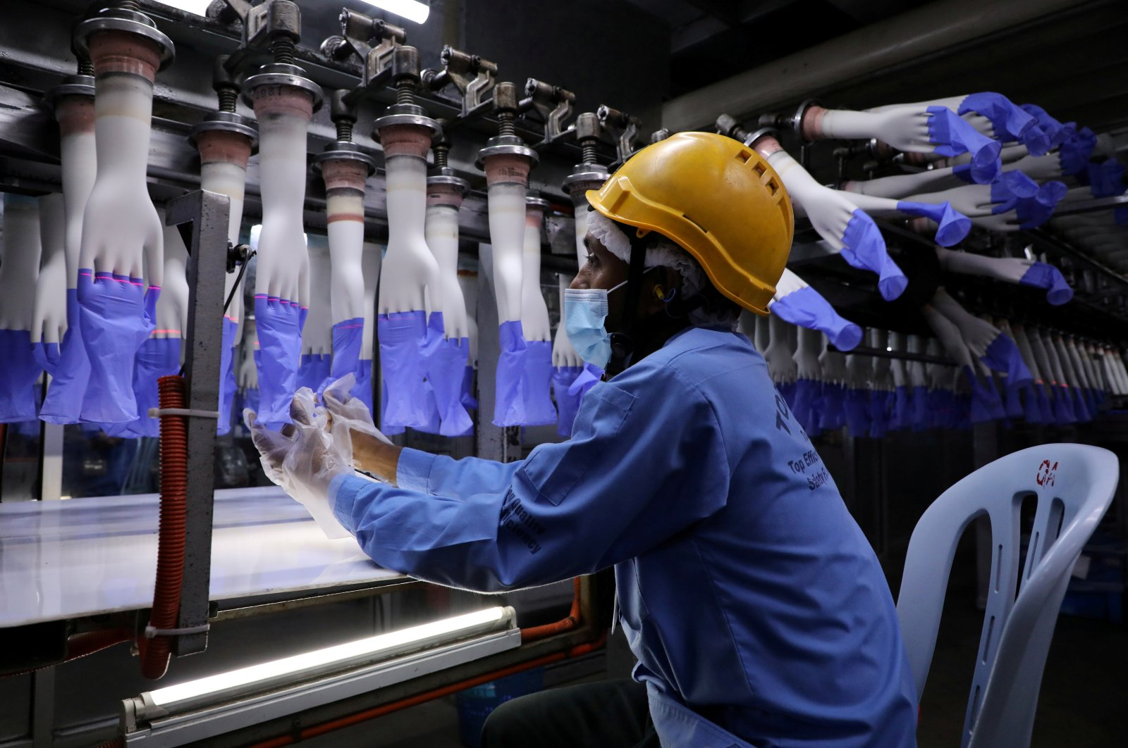 A worker inspects newly-made gloves at Top Glove factory in Shah Alam, Malaysia, Aug. 26, 2020. (Reuters Photo)