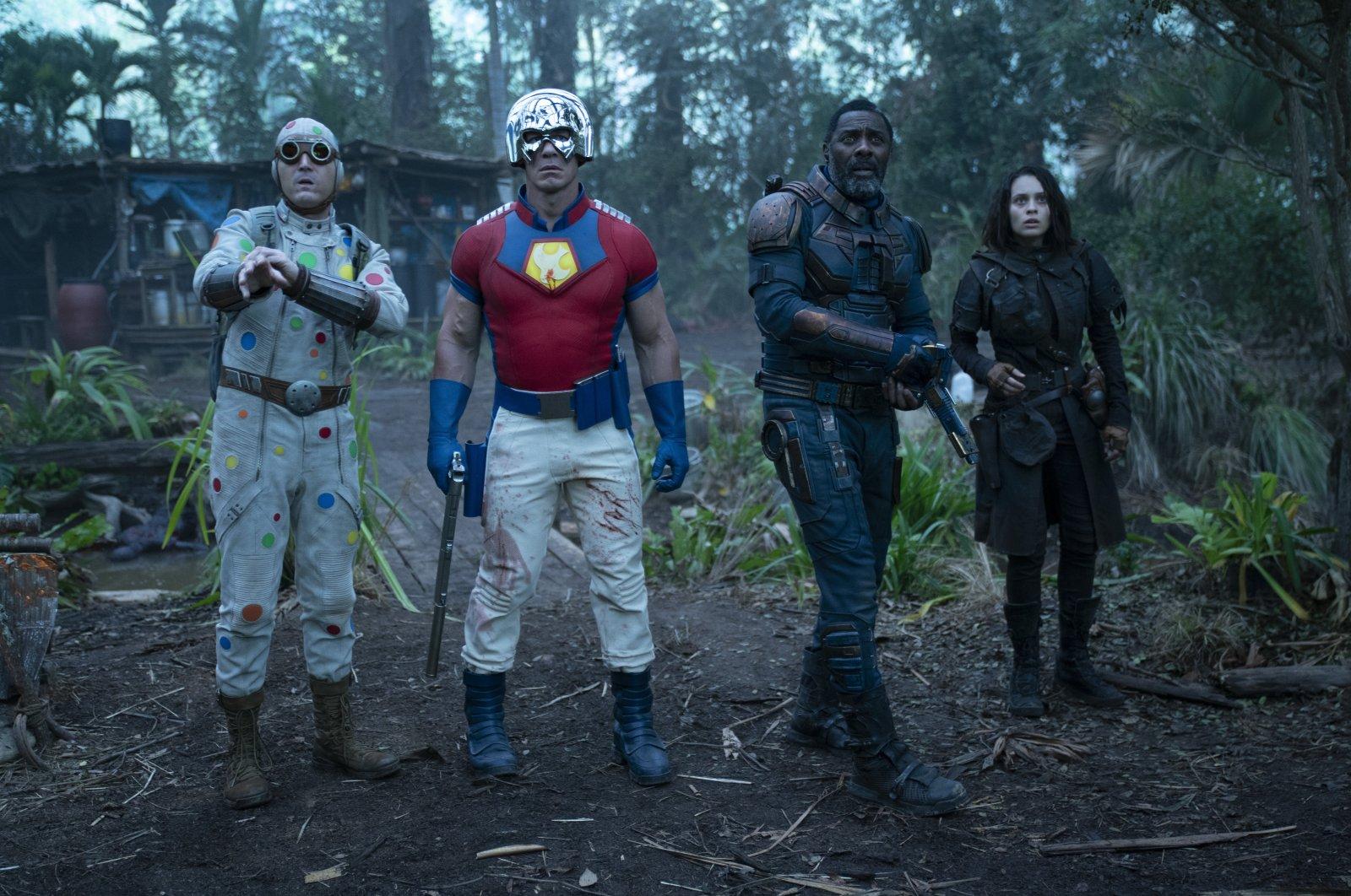 "David Dastmalchian (L), John Cena (C-L), Idris Elba (C-R) and Daniela Melchior look off camerain a scene from the film ""The Suicide Squad."" (Warner Bros. via AP)"