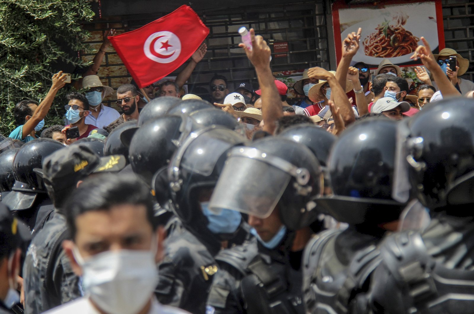 Protesters face Tunisian police officers during a demonstration in Tunis, Tunisia, Sunday, July 25, 2021. (AP Photo)