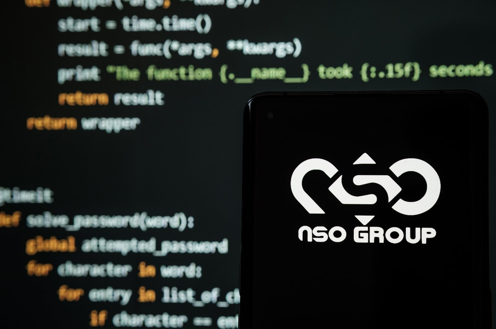 NSO Group logo seen on a smartphone placed in front of a laptop with a simple hacking code, Stafford, United Kingdom, July 19, 2021. (Shutterstock Photo)