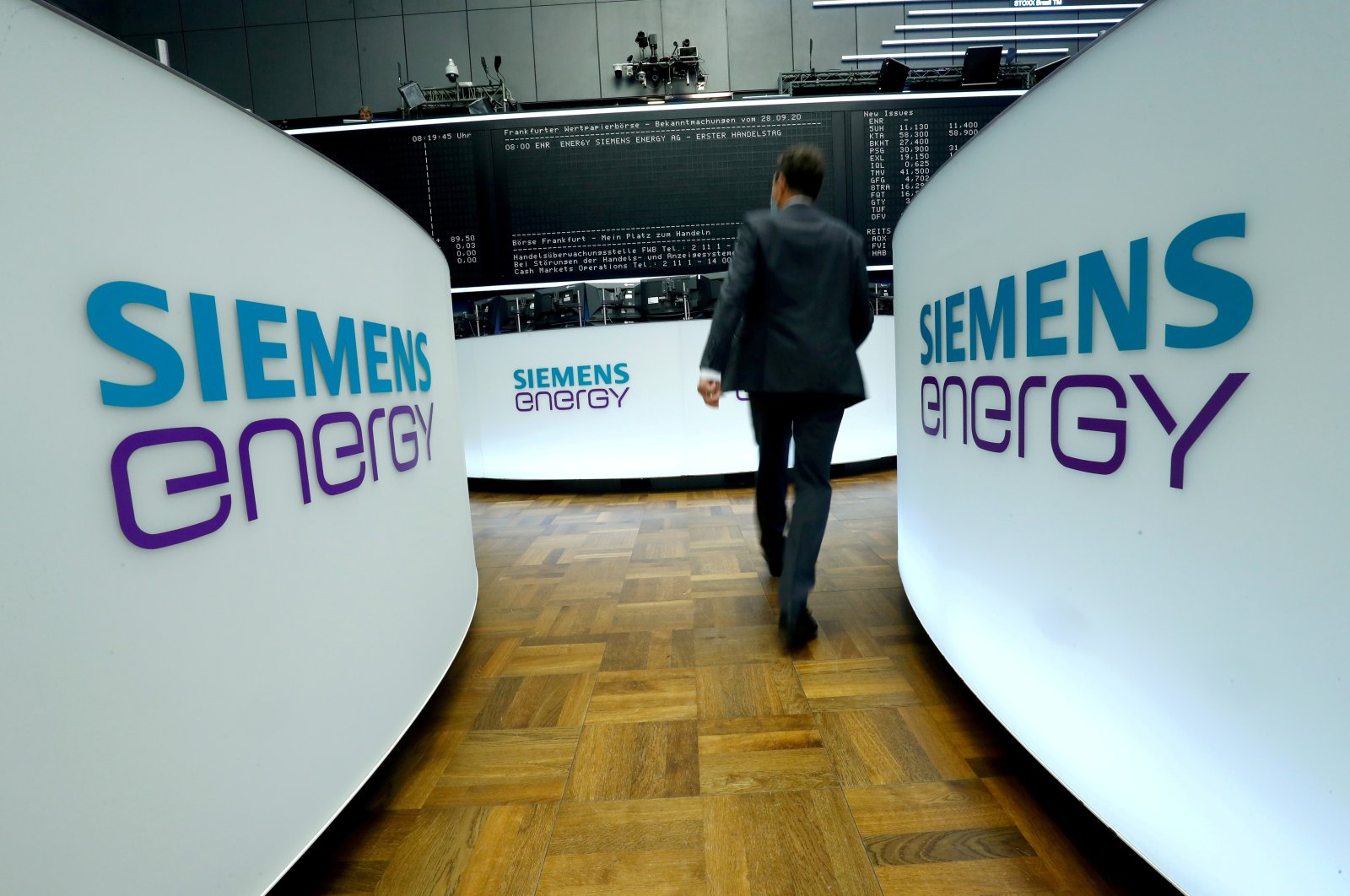 A trader walks next to Siemens Energy AG logos during Siemens Energy's initial public offering (IPO) at the Frankfurt Stock Exchange in Frankfurt, Germany, Sept. 28, 2020.  (Reuters Photo)