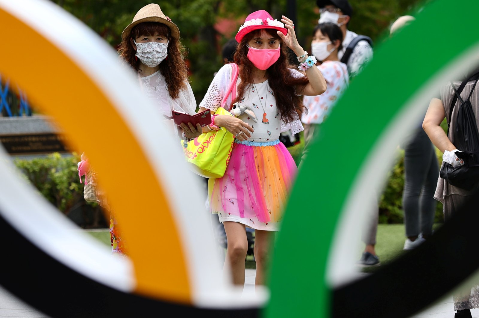 People in protective face masks against COVID-19 visit an Olympic Ring outside the National Stadium, the main venue of the Tokyo 2020 Olympic Games, Tokyo, Japan, Aug. 3, 2021. (Reuters Photo)