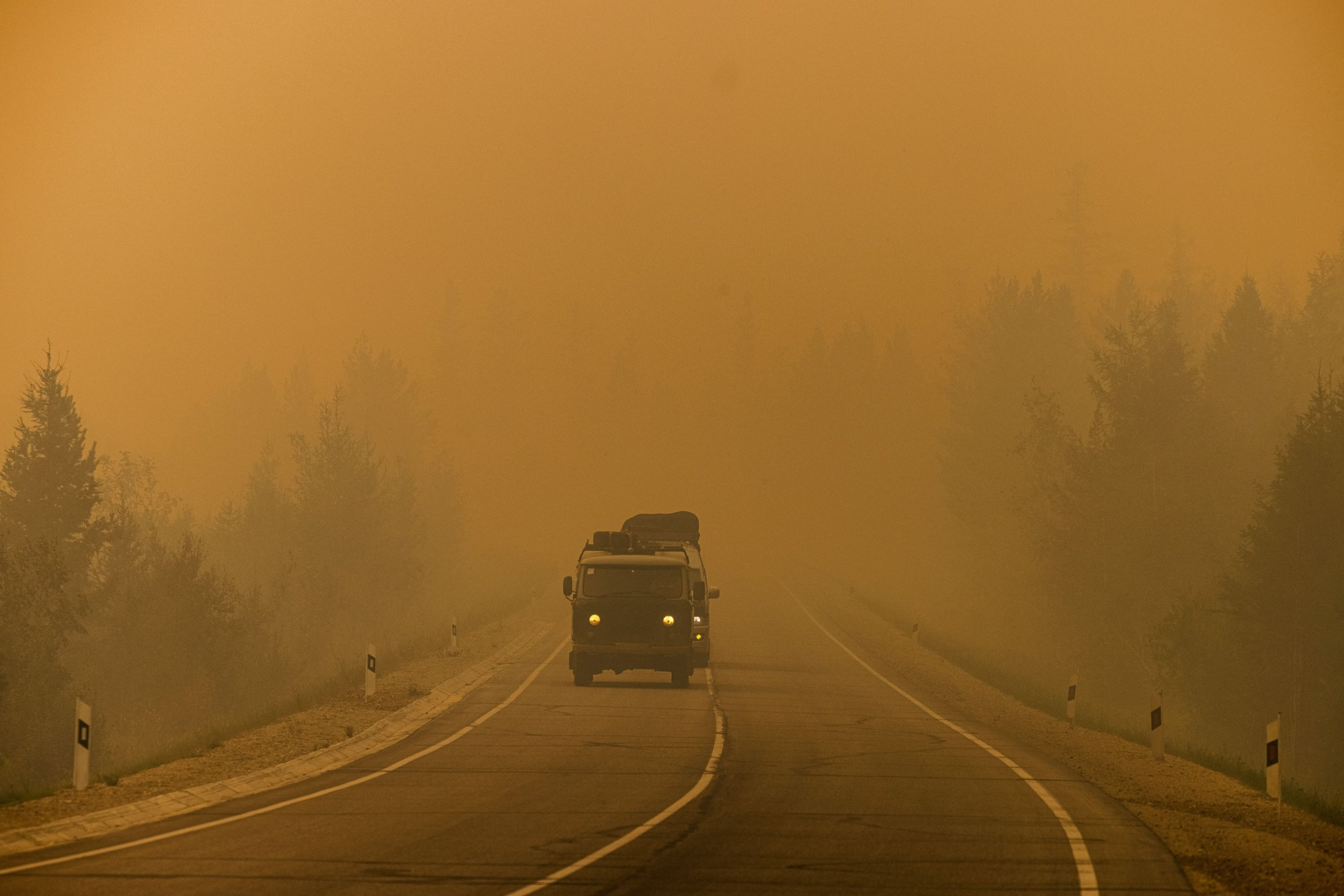 Cars drive down a road covered with smoke from nearby forest fires between the village of Magaras and the city of Yakutsk, in the Republic of Sakha, Siberia, Russia, July 27, 2021. (AFP Photo)
