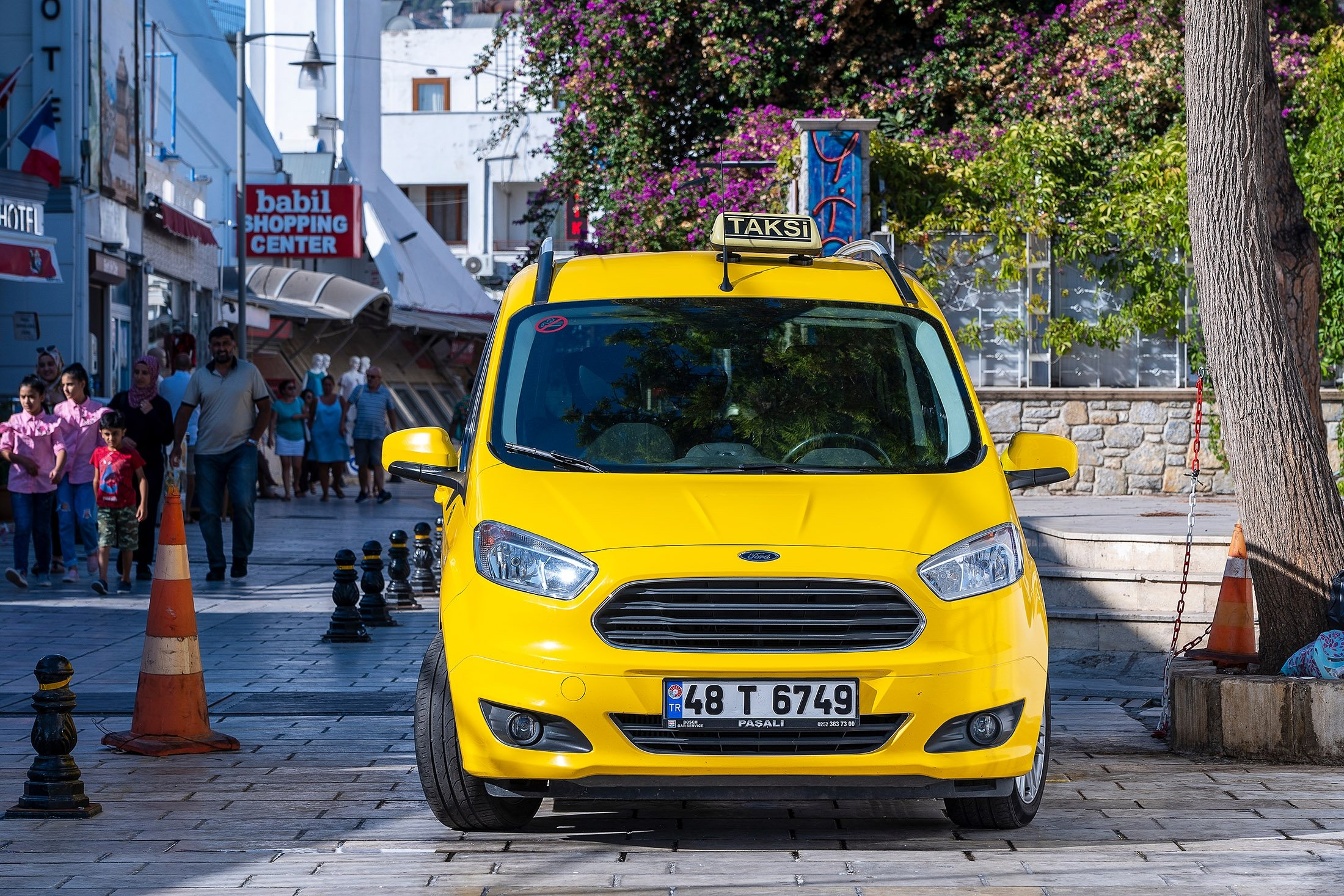 A yellow taxi car is parked on a street in the old town of Bodrum, Turkey. (Shutterstock Photo)