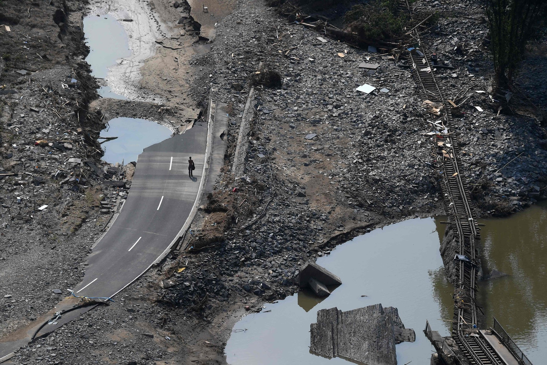A man walks along the destroyed B267 federal highway, along a destroyed railway track, in the district of Ahrweiler, days after heavy floods caused major damage in the region, Germany, July 23, 2021. (AFP Photo)