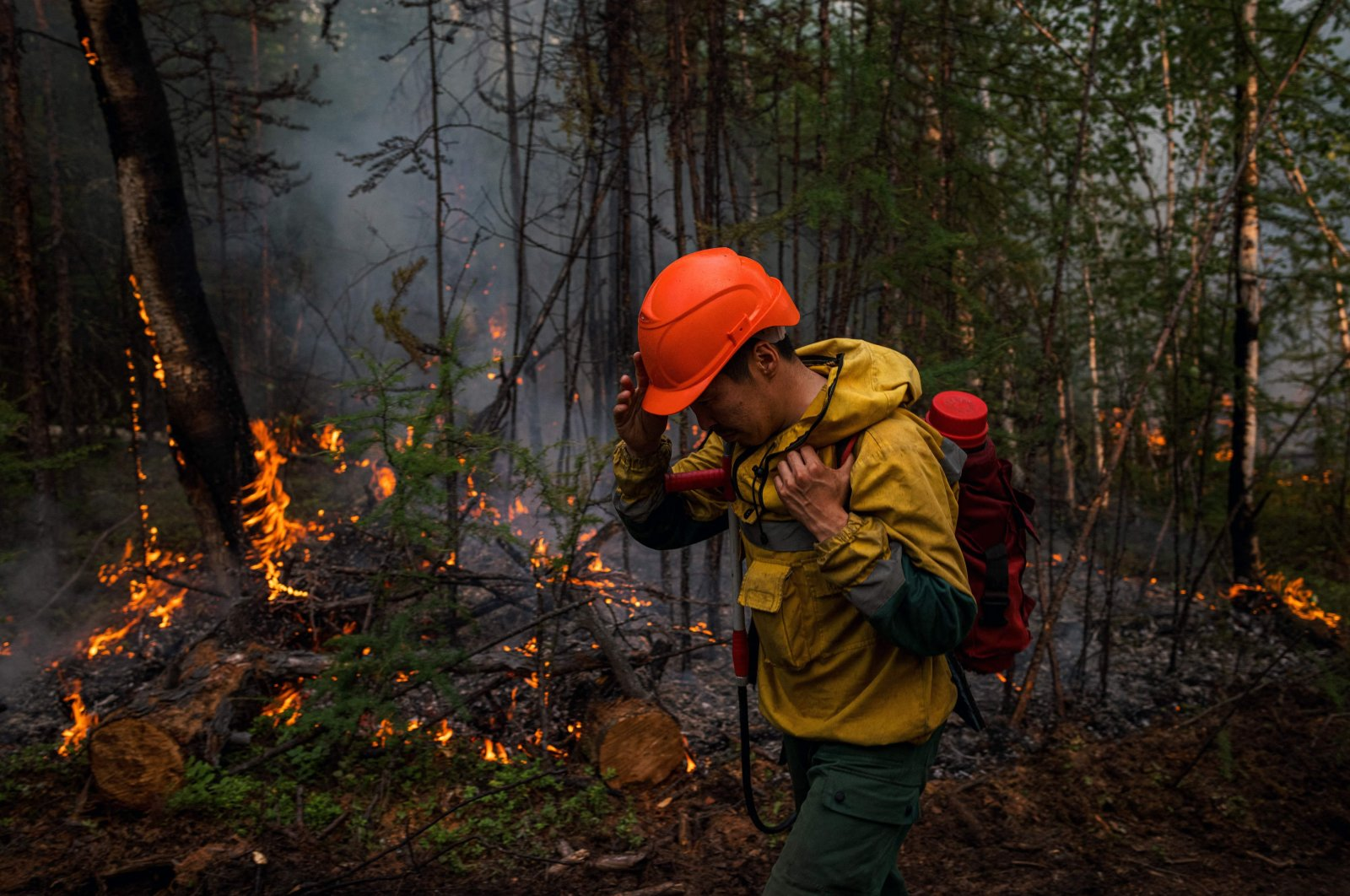 A member of the Aerial Forest Protection Service monitors a backfire at the edge of the village of Byas-Kyuel, Russia, July 26, 2021. (AFP Photo)