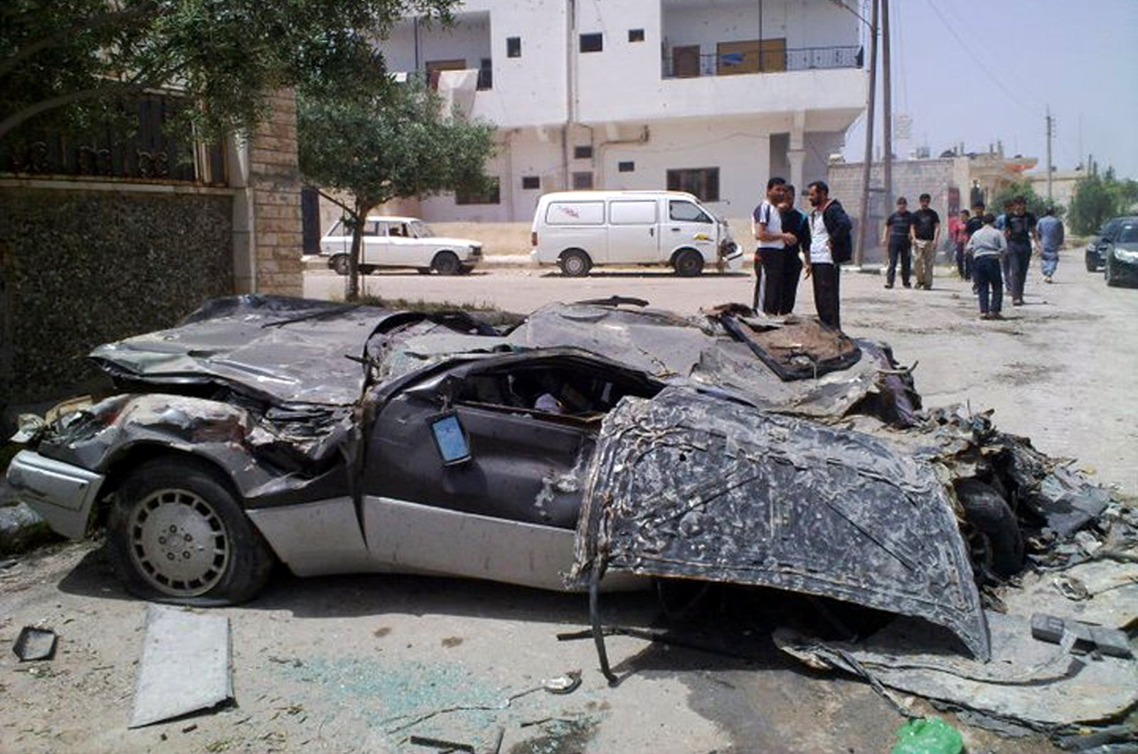 In this undated citizen journalism image made on a mobile phone and acquired by the AP, Syrians gather near a damaged car in the southern city of Daraa, Syria. (AP File Photo)
