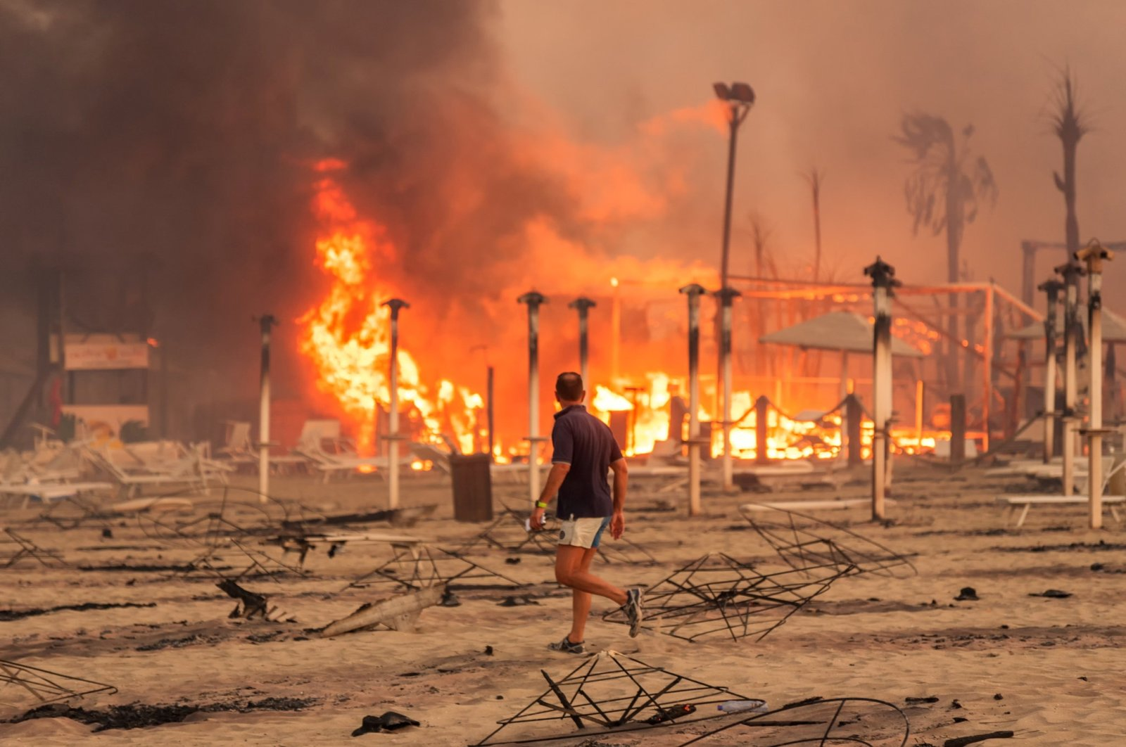 A man walks in front of a fire at Le Capannine beach in Catania, Sicily, Italy, July 30, 2021.  (Roberto Viglianisi via Reuters)