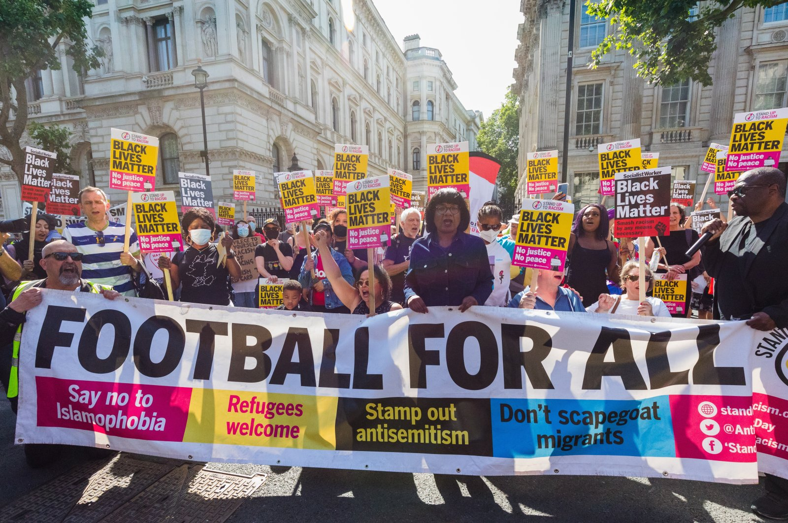 """British Member of Parliament Diane Abbott (C) joins demonstrators from """"Stand Up To Racism"""" as they stage an anti-racism and 'taking the knee' protest against the British government and in solidarity with England footballers Marcus Rashford, Bukayo Saka and Jadon Sancho outside Downing Street in London, England, July 17, 2021. (EPA Photo)"""
