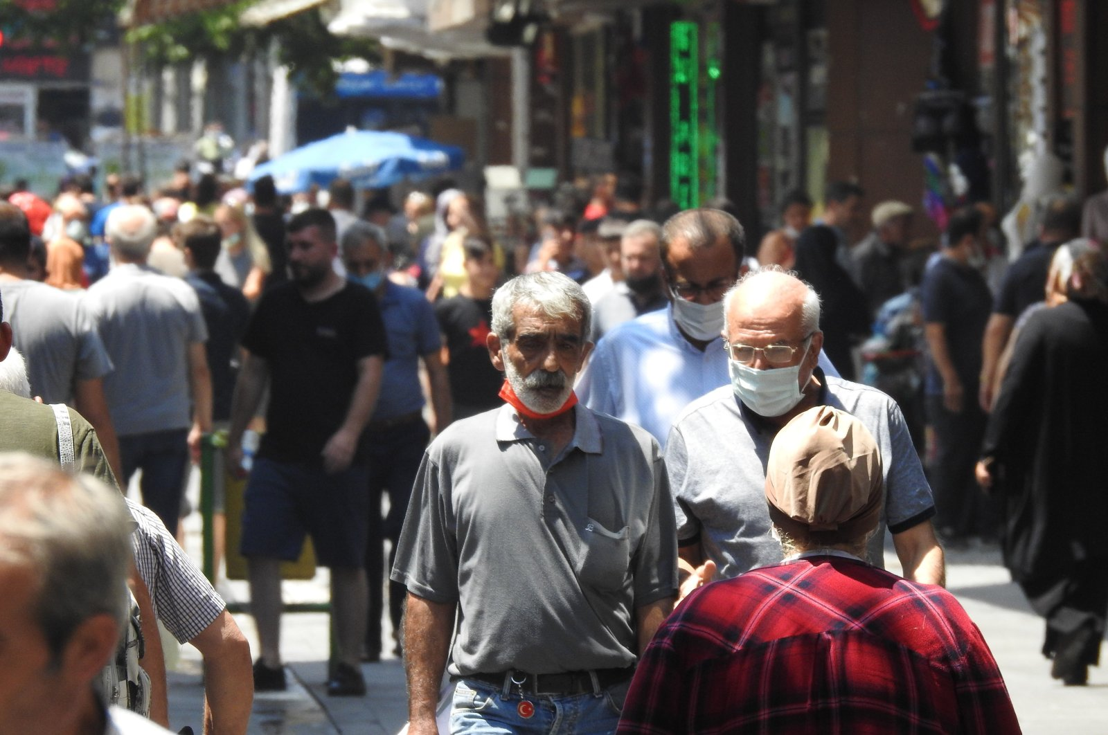 People wearing protective masks walk on a street in Gaziantep, Turkey, Aug. 3, 2021. (IHA PHOTO)