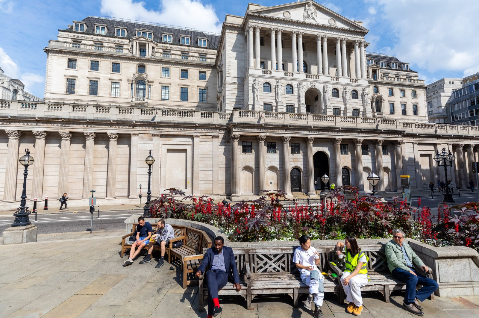 People sit in front of the Bank of England in London, U.K., Aug. 4, 2021. (EPA Photo)