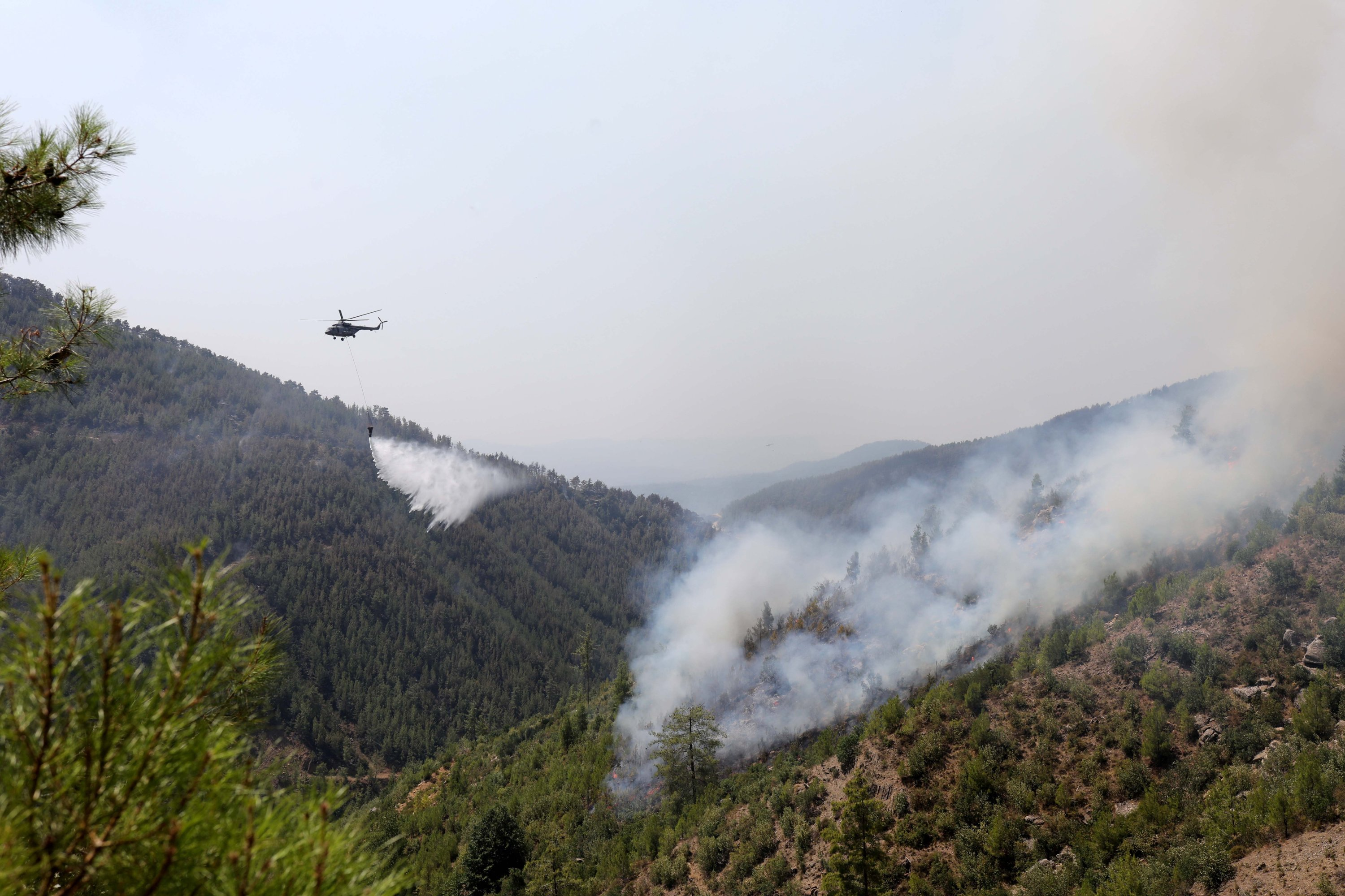 A helicopter dumps water on a forest fire, in Antalya, southern Turkey, Aug. 6, 2021. (DHA PHOTO)