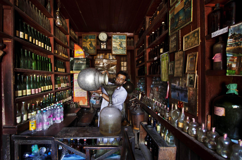 Abdul Aziz Kozgar pours local syrup into a glass jar at his shop in Srinagar, Kashmir, June 23, 2012. (AP Photo)