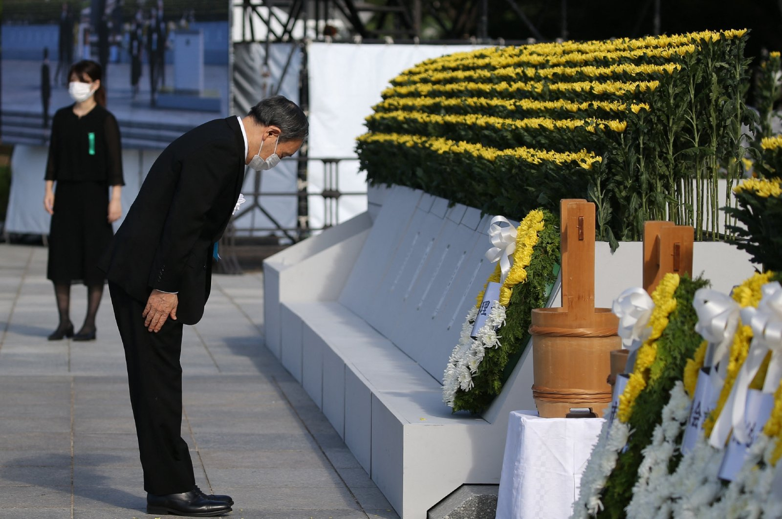 Japan's Prime Minister Yoshihide Suga (L) pays his respects during a ceremony to mark the 76th anniversary of the world's first atomic bomb attack at the Peace Memorial Park in Hiroshima on Aug. 6, 2021. (AFP Photo)