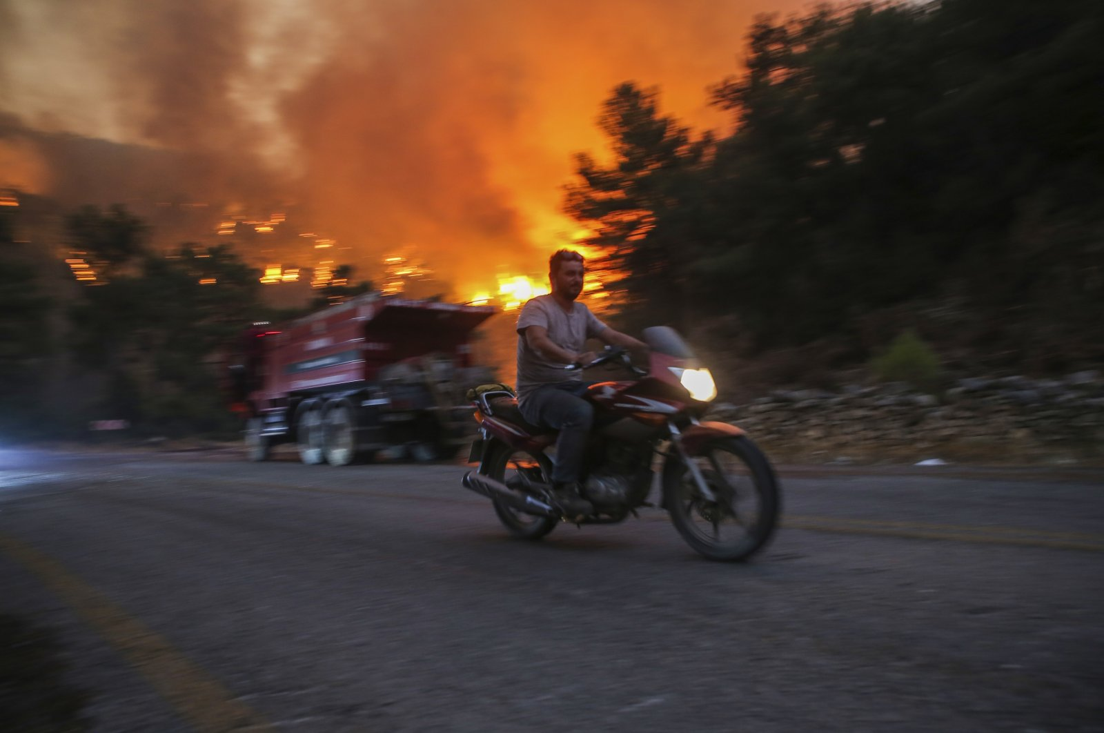 A man rides away from an advancing fire in Çökertme village, near Bodrum, Muğla province, Turkey, Aug. 2, 2021. (AP Photo)