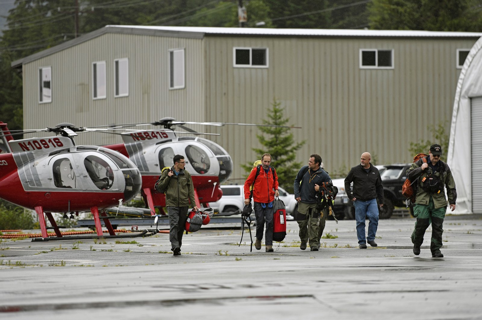 Ketchikan Volunteer Rescue Squad personnel land and disembark from a Hughes 369D helicopter at Temsco Helicopters Inc in Ketchikan, Alaska, Aug. 5, 2021. (AP Photo)