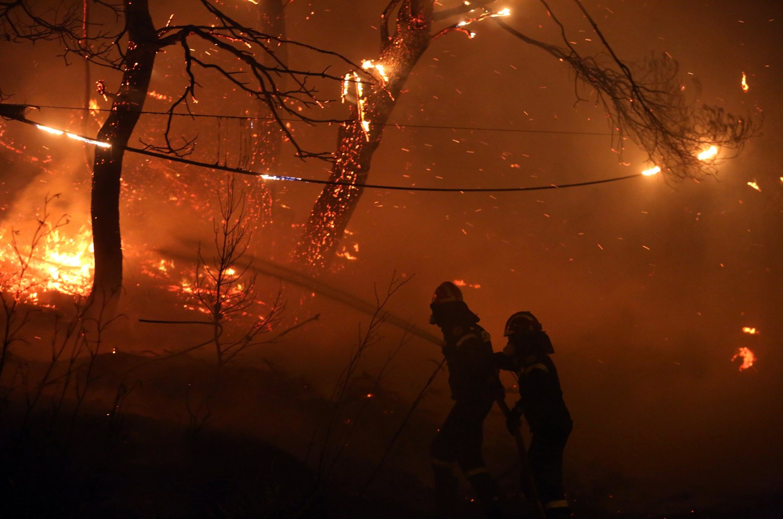 Two firefighters try to prevent a wildfire from crossing into the national highway, in the area of Afidnes, northeastern of Athens, Greece, Aug. 5, 2021. (EPA Photo)