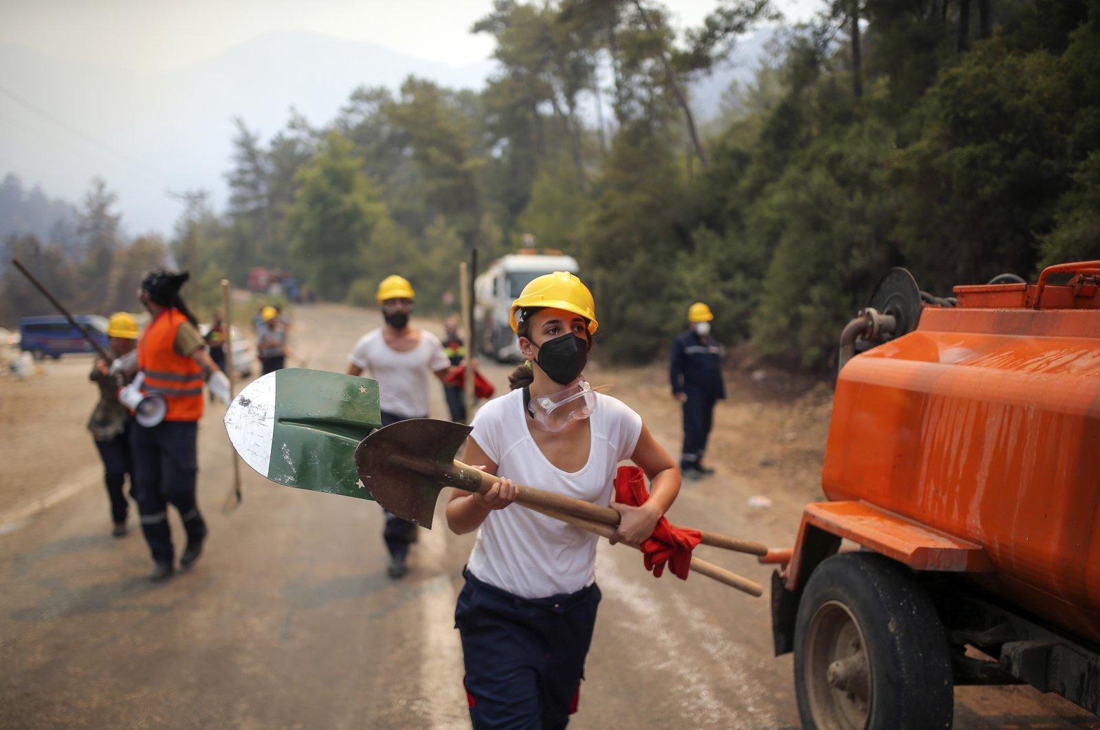 Volunteers run as they fight wildfires in Turgut village, near tourist resort of Marmaris, in Muğla, southwestern Turkey, Aug. 4, 2021. (AP PHOTO)