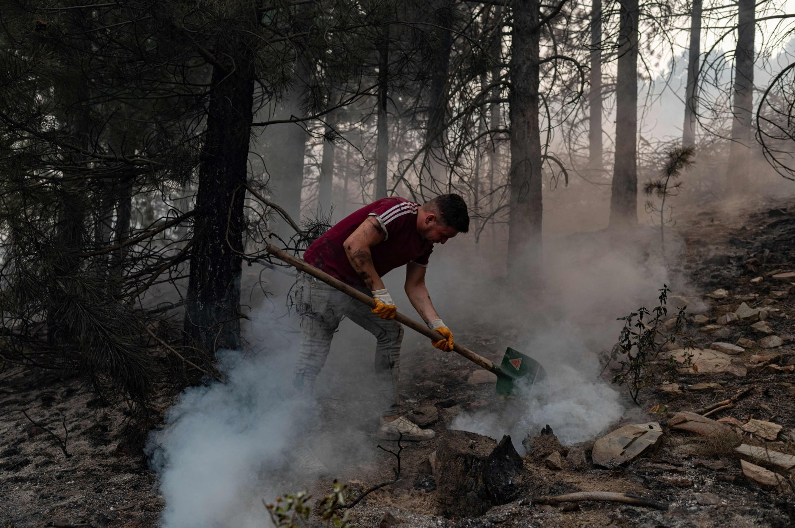 A volunteer from a nearby village uses a shovel to help contain smouldering forest fires in the hills of a recently burnt area near Kavaklıdere, a town in Muğla province, Turkey, Aug. 5, 2021. (AFP Photo)