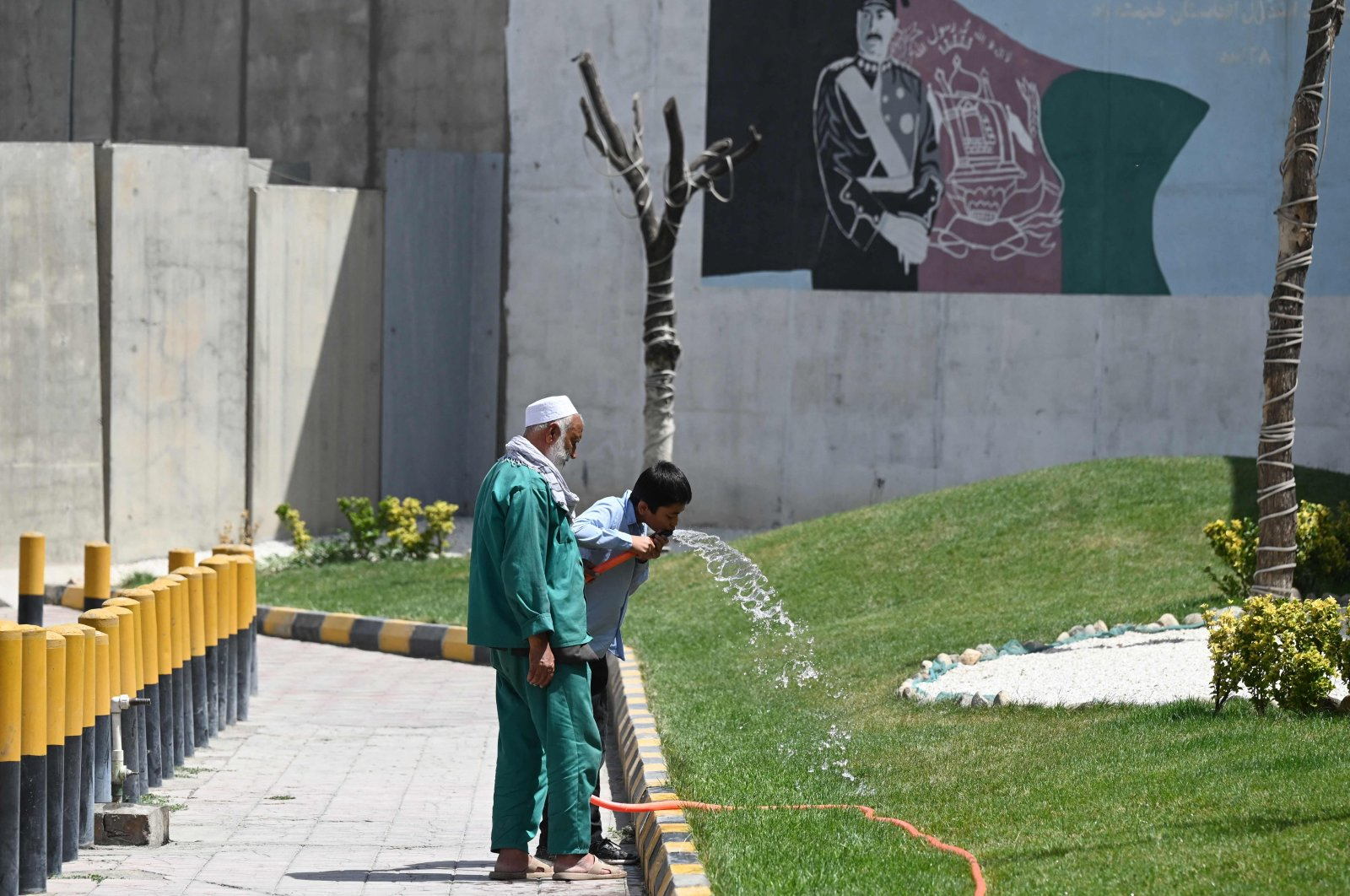 A schoolboy drinks water from a pipe as a gardener looks on, Kabul, Afghanistan, Aug. 5, 2021. (AFP Photo)