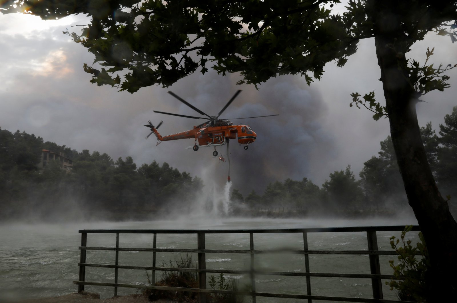 A firefighting helicopter is filled with water from Beletsi Lake as a wildfire erupts near the village of Ippokratios Politia, north of Athens, Greece, Aug. 6, 2021. (Reuters Photo)