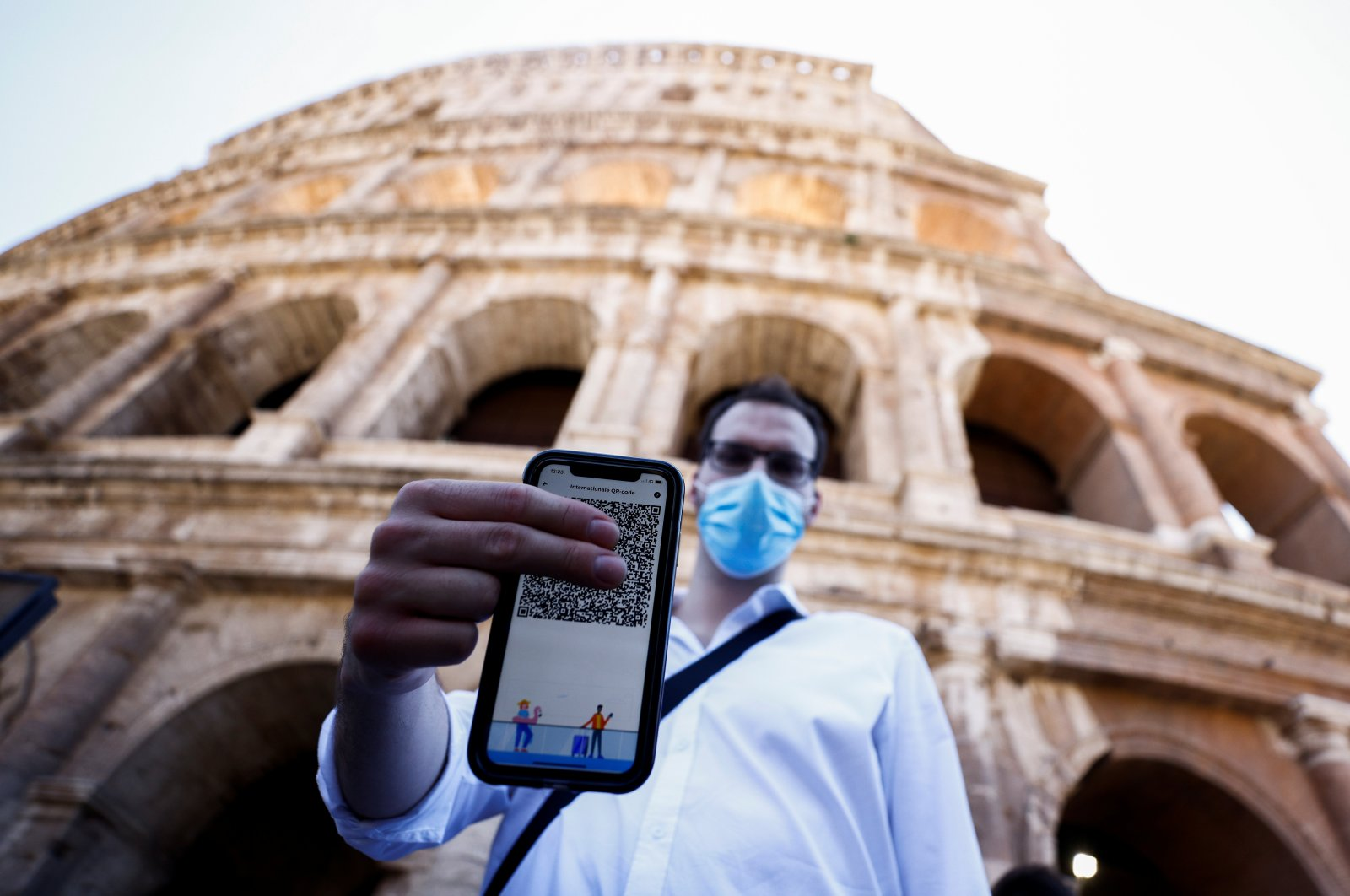 A man shows his Green Pass (health pass) before entering the Colosseum as Italy brings in tougher restrictions where proof of immunity will be required to access an array of services and leisure activities in Rome, Italy, August 6, 2021. (Reuters Photo)