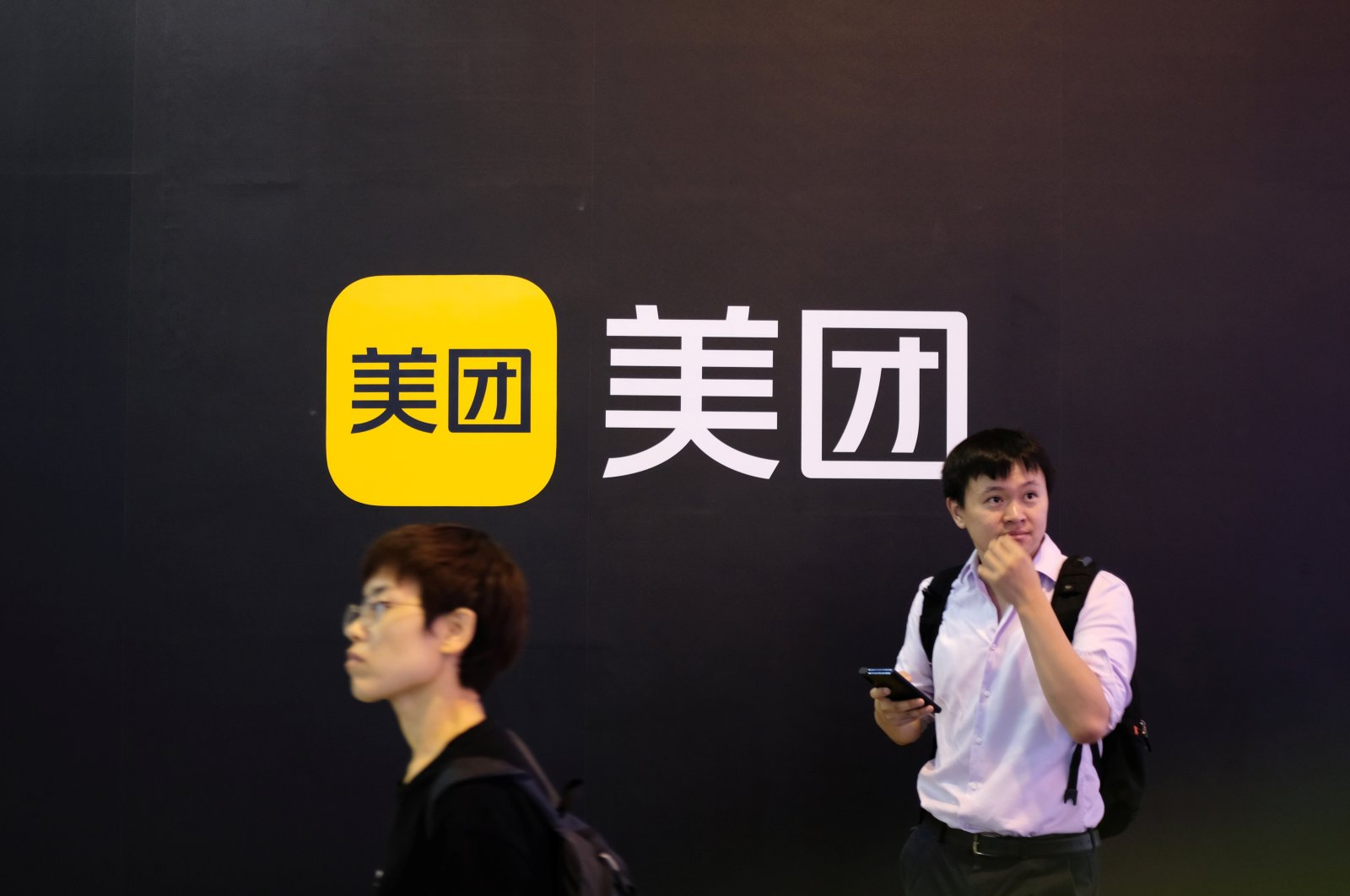 People walk past a Meituan logo at the World Artificial Intelligence Conference (WAIC) in Shanghai, China, July 8, 2021. (Reuters Photo)