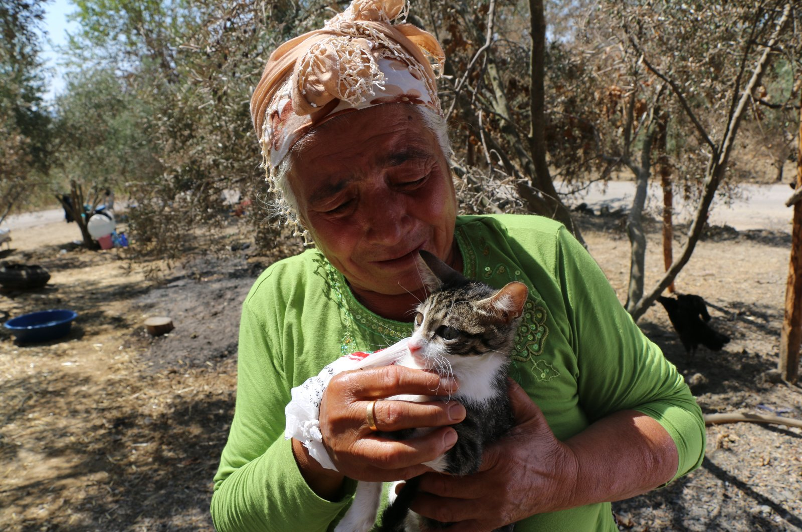 """Fatma Duysak pets her cat """"Hayat"""" who recovered after suffering injuries due to the wildfire, in Aladağ district, in Adana, southern Turkey, Aug. 6, 2021. (AA PHOTO)"""
