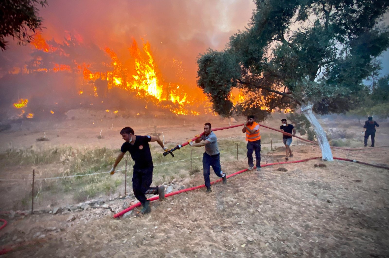 Firemen and local volunteers carry hosepipes as they fight to extinguish a wildfire in Ören, in the holiday region of Muğla, southwestern Turkey, Aug. 6, 2021. (AFP Photo)