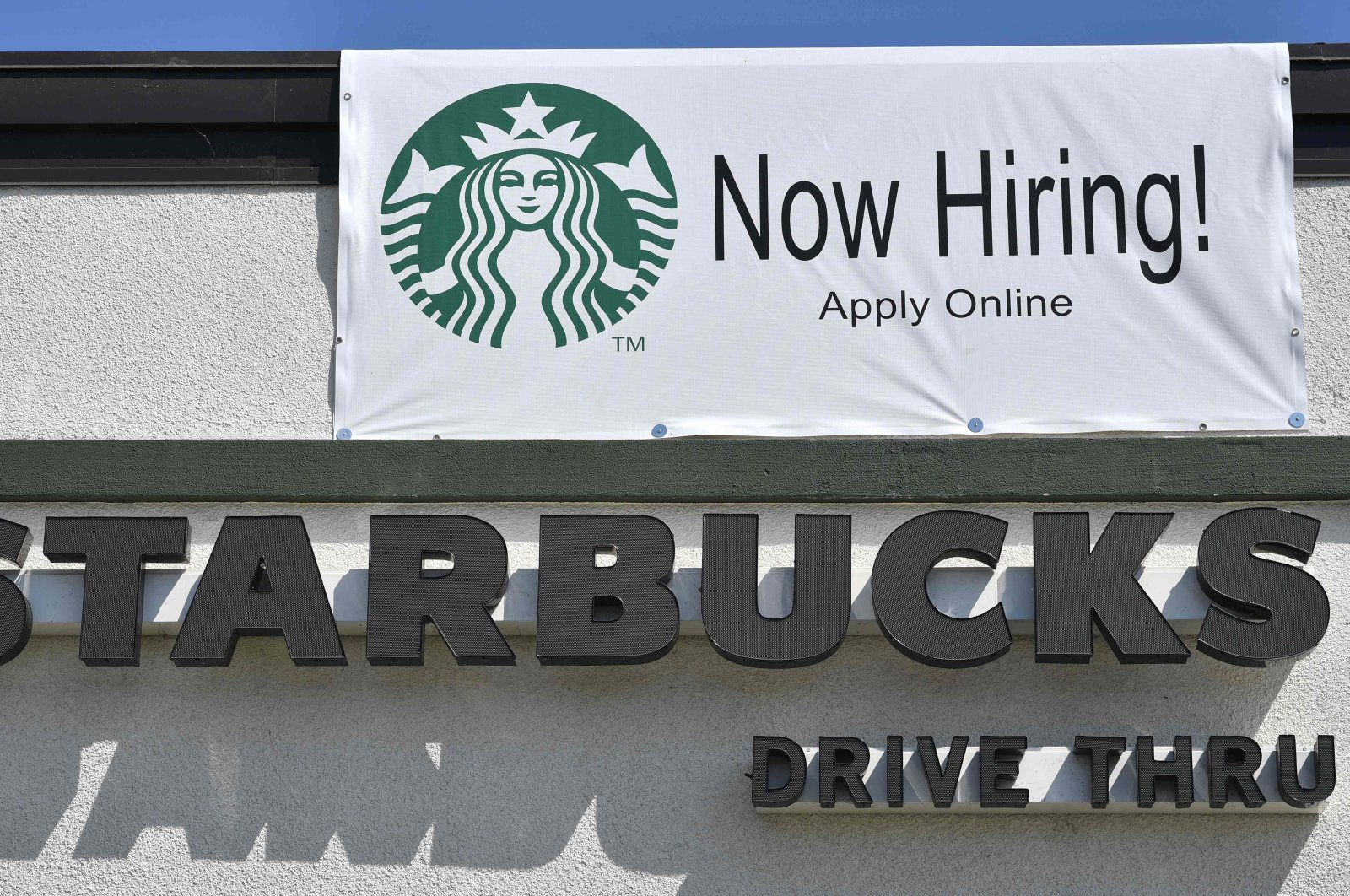 """A """"Now Hiring"""" sign is displayed outside a Starbucks coffee shop in Glendale, California, US, July 7, 2021. (AFP Photo)"""