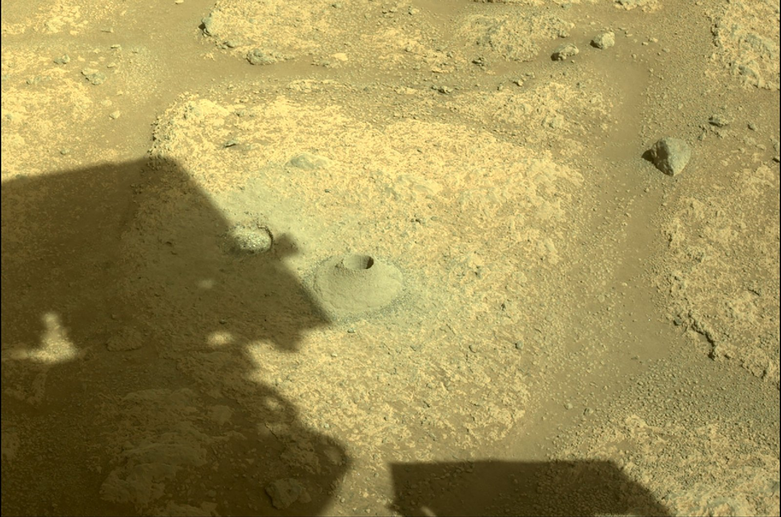 The shadow of the Perseverance Mars rover is cast next to its first hole drilled in a rock, Aug. 6, 2021. (AFP Photo/NASA/JPL-Caltech)