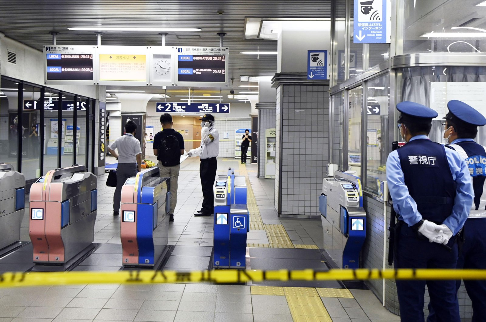 Policemen stand as ticket gates are sealed off at Soshigaya Okura Station after stabbing on a commuter train, in Tokyo, Aug. 6, 2021. (Kyodo News via AP)