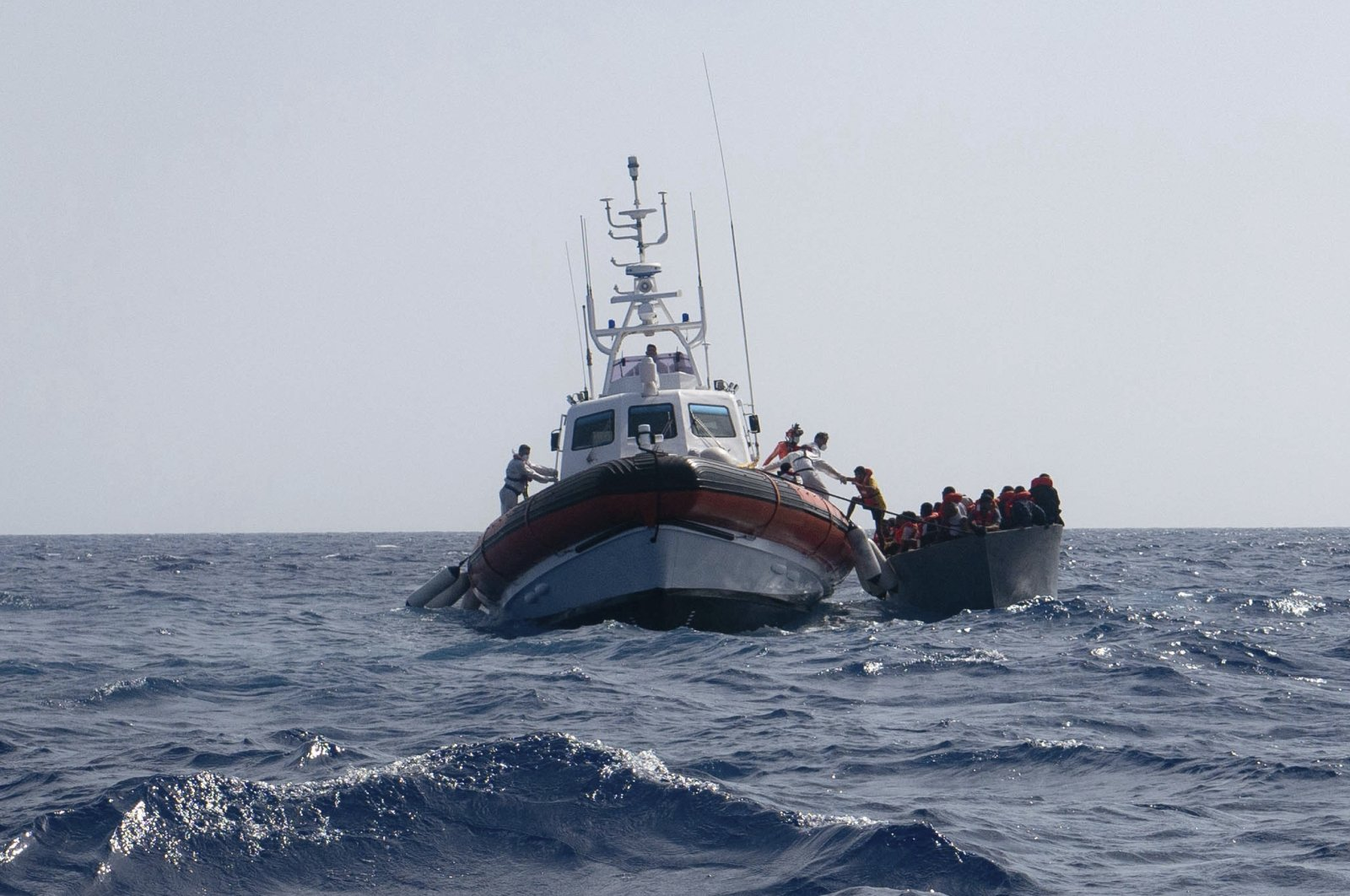 A boat overcrowded with migrants is being rescued by German charity boat Sea-Watch 3 in the Mediterranean sea, Aug. 2, 2021. (Sea-Watch.org via AP)