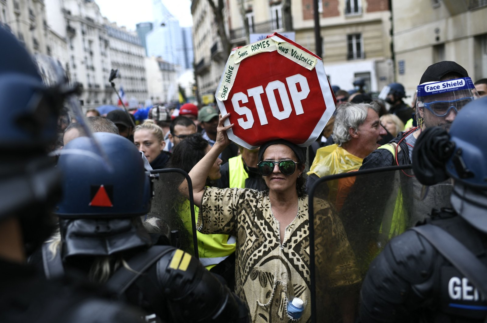 A protestor holds a sign reading 'Without hatred weapon or violence - Stop' in front of riot forces during a demonstration, part of a national day of protest against the mandatory COVID-19 health pass to access most of the public space, near the Pont de Neuilly, the suburb of Neuilly-sur-Seine, western Paris, Aug. 7, 2021. (AFP Photo)
