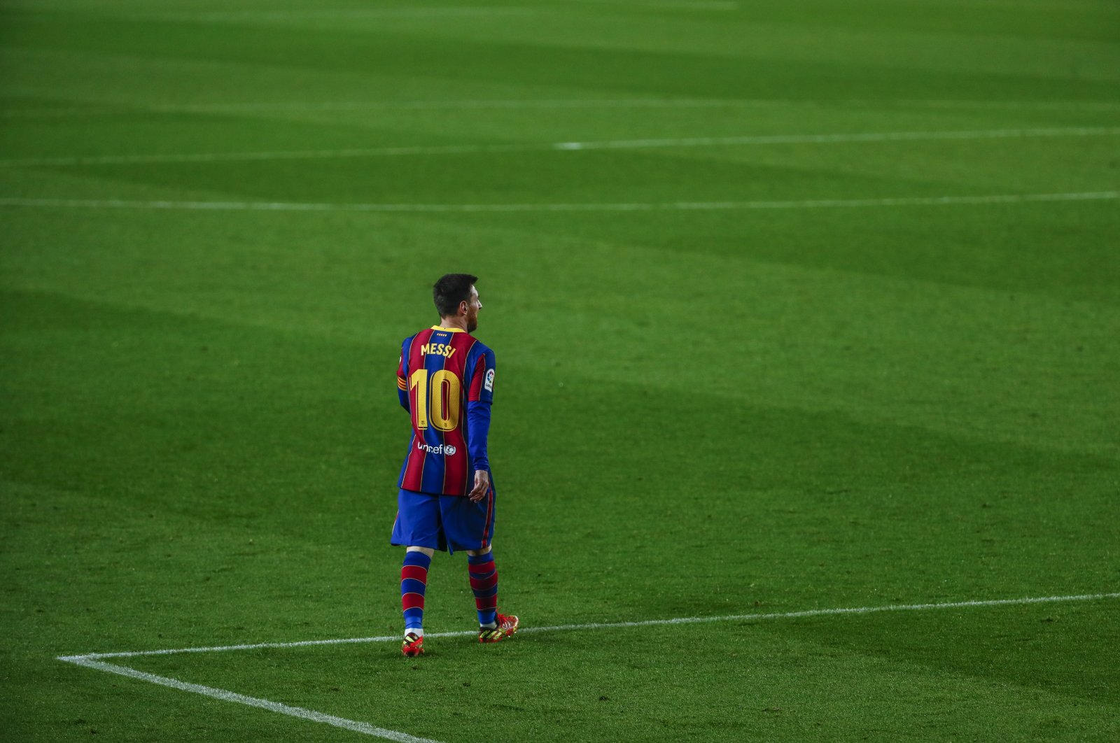 Barcelona's Lionel Messi walks on the pitch,  during the Spanish La Liga football match between FC Barcelona and Huesca at the Camp Nou stadium in Barcelona, Spain, March 15, 2021. (AP Photo)