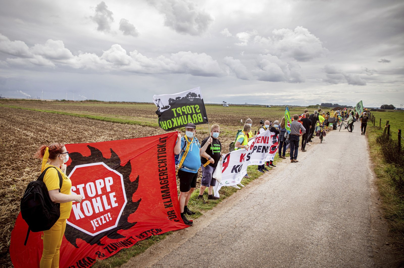 Environmental and climate activists, as well as residents of neighboring villages, form a human chain on the edge of the Garzweiler open-cast mine in Juechen, Germany, Aug. 7, 2021.  (Malte Krudewig/dpa via AP)
