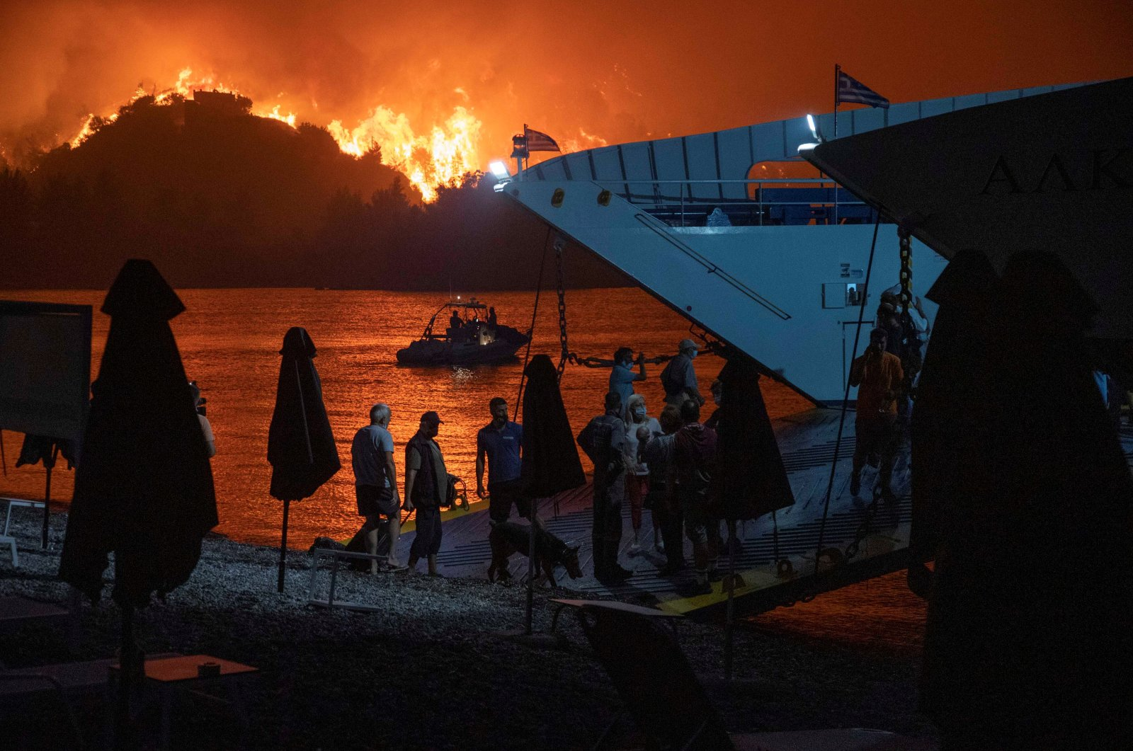 People board a ferry during evacuation as a wildfire burns in the village of Limni, on the island of Evia, Greece, Aug. 6, 2021. (Reuters Photo)