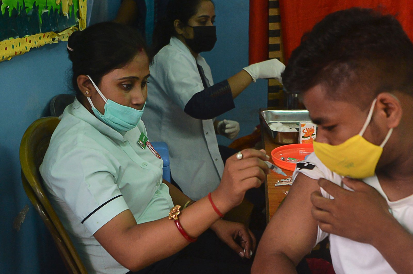 A healthcare worker inoculates a man against COVID-19 at the Bright Academy school in Siliguri, India, Aug. 7, 2021. (Photo by Diptendu DUTTA / AFP)