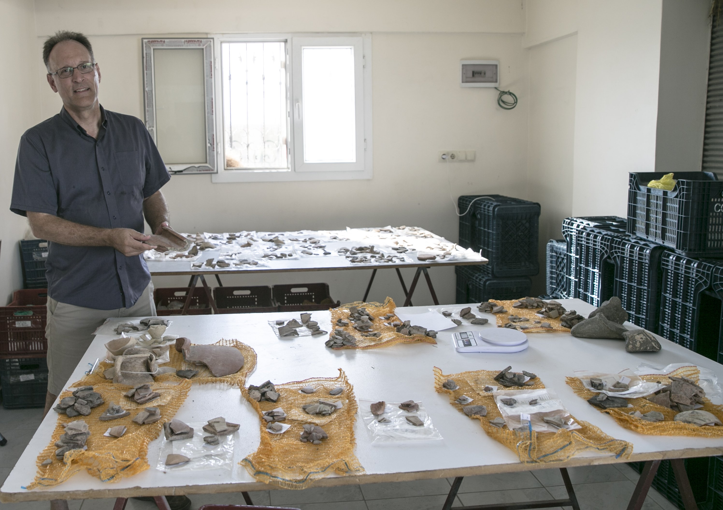 Professor Timothy Harrison poses with archaeological finds that they unearthed in Tell Tayinat, Hatay, southern Turkey, August 8, 2021. (AA Photo)