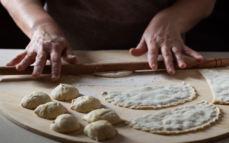 A woman rolls dough to prepare çiğ börek. (Shutterstock Photo)